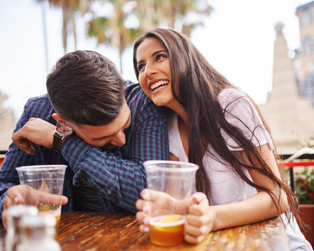 hispanic couple laughing and having fun while drinking beer