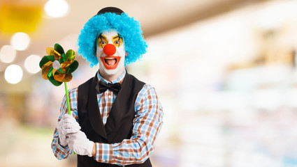 portrait of a funny clown holding a pinwheel