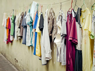 Old clothes hangers and colorful clothes in the sunlight, Selective focus