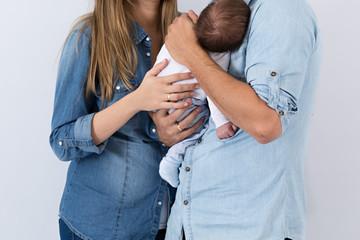 Bebé en brazos de sus padres.