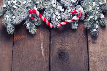 Spruce branches and decorative candy cane on aged wooden  backgr