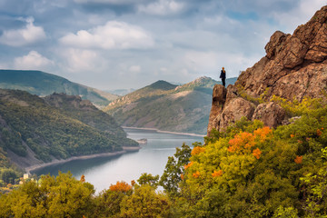 Autumn from the top. A woman on the top of a rock enjoys the view of an autumn forest and Studen Kladenec dam, Bulgaria.