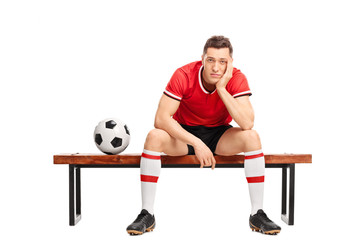 Sad young football player sitting on a bench