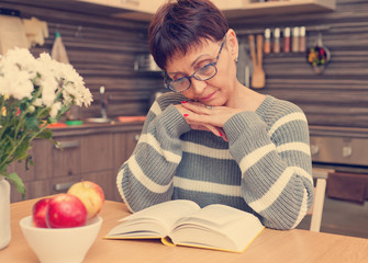 woman 50 years old reading a book in the kitchen