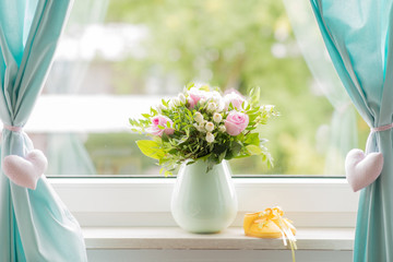 beautiful bouquet and yellow small baby shoe on a window sill