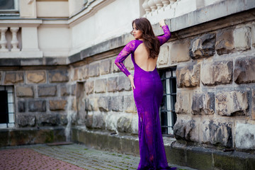 beautiful girl in the purple dress leaned on the wall