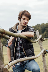 young man next to a wooden fence