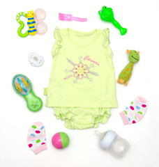 top view of baby girl green clothes and toy stuff