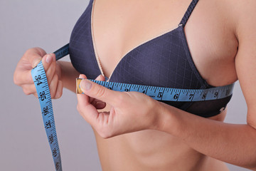 Woman measuring her breast size.