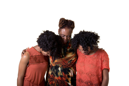 A mother and her 2 daughters praying isolated on white