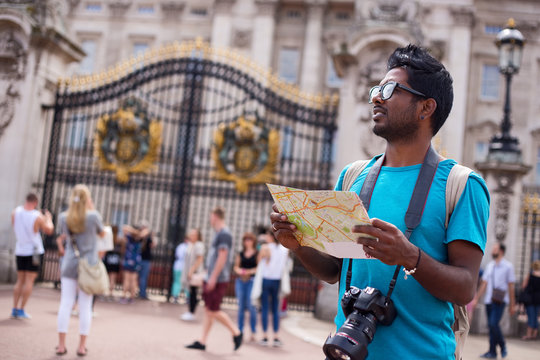 Indian tourist outside buckingham palace holding a map and his camera