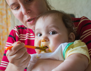 Little baby mother feeding baby food from a spoon.