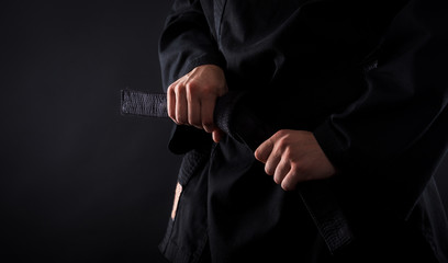Garden Poster Martial arts Closeup of male karate fighter tying the knot to his black belt