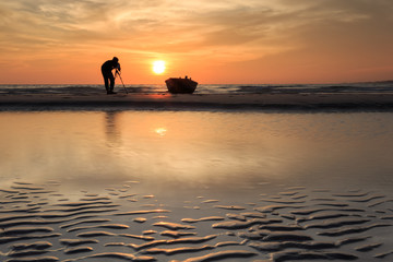Photographer shooting the Boats at the beach during sunset