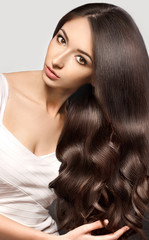 Beautiful woman with Healthy Brown Hair.  Beauty Model brunette girl touching her long smooth shiny hair. Gorgeous Hair. Hairstyle. Hair cosmetics, haircare.