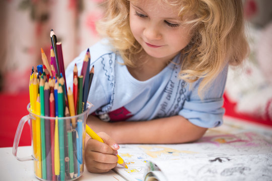 Portrait of child girl drawing with colorful pencils