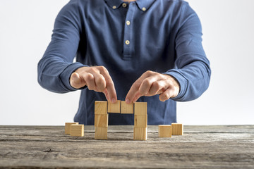 Front view of a man making a bridge with wooden cubes