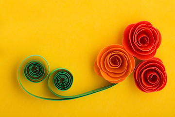 Paper rose flowers made with quilling technique on yellow backgr