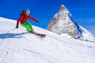Skier skiing downhill against Matterhorn peak in Switzerland