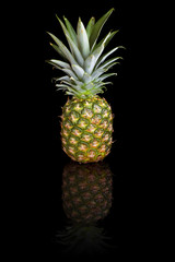 Pineapple on a black reflective background