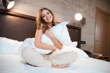 Curly smiling woman sitting on a bed and hugging pillow