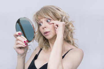 Older blonde woman checking her wrinkles in a mirror
