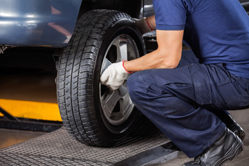 Mechanic Fixing Car Tire At Repair Shop Wall mural