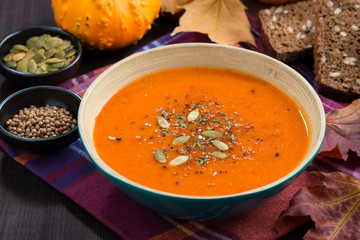 pumpkin soup in a bowl on wooden table
