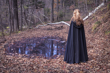 Girl wearing mantle standing by the water