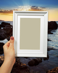 Wooden frame in woman hands on the background sunset
