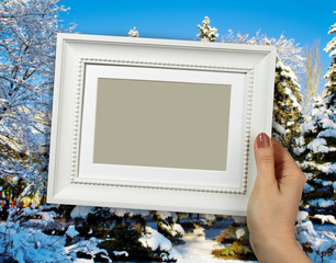 Wooden frame in woman hands on the winter forest background