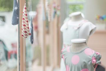young girl fashion dress in childrenswear fashion shop window