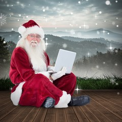 Composite image of santa sits and uses a laptop