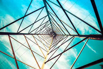 Silhouette shot of electricity pylons with cloudy sky