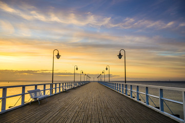 wooden pier by the sea lit by stylish lamps at night  - fototapety na wymiar