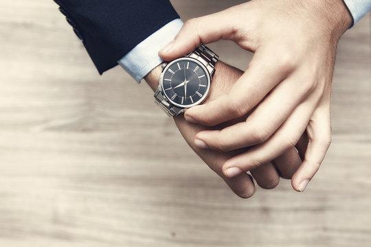 mano di uomo con al polso orologio, con camicia e giacca elegante per lavoro
