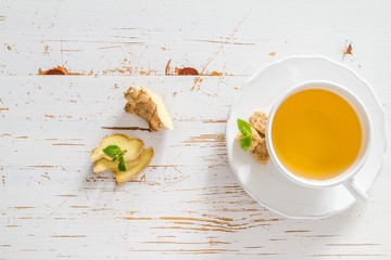 Ginger tea and ingredients on white wood background