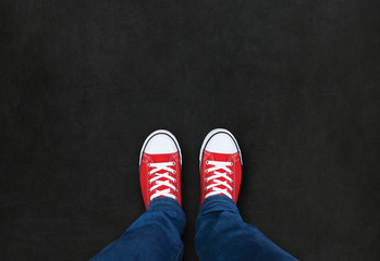 Feet wearing red shoes on black background with space for text