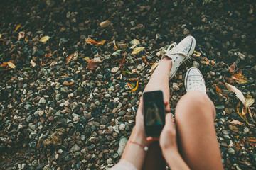 Young hipster girl making a photo of legs with a smartphone on rocky coast background. Feet selfie with copy space.