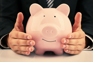 Man with piggy-bank on white background