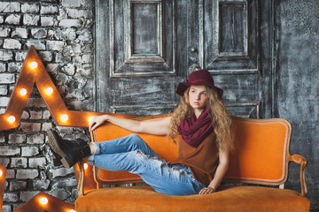 Beautiful curly-haired girl in hat and jeans
