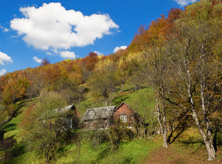 Mystical landscape with a hut on the hill in autumn on a backgro