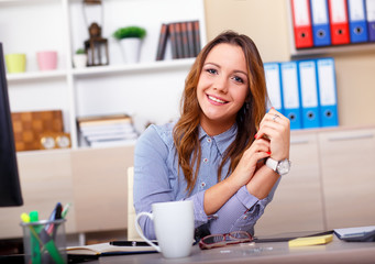 Portrait of attractive woman working in office, she siting at office desk.