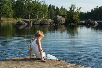 Boy relaxing on a jetty. He's sitting in the sunshine and looking out over the beautiful lake Skiren in the swedish countryside.