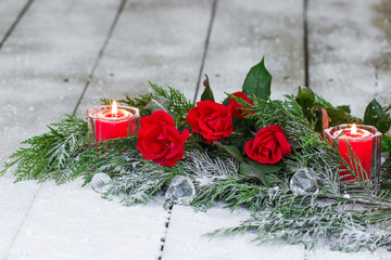 Red roses, Christmas candles and green garland on winter background