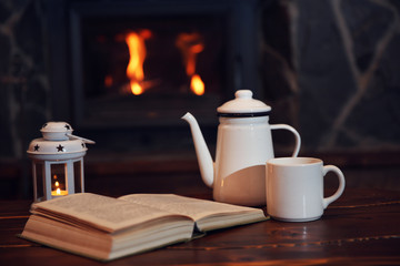 Hot tea or coffee in mug, book and candles on vintage wood table. Fireplace as background