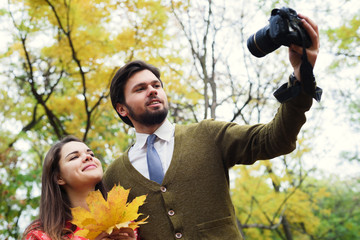young happy couple making selfie using camera in autumn park