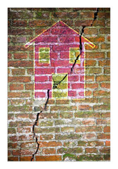 Cracked brick wall with a colored house drawn on it in puzzle shape