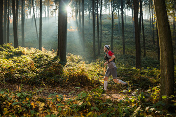 man running in the autumn forest with morning sun rays
