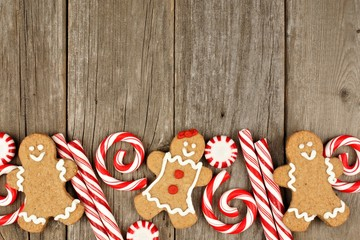 Christmas gingerbread cookies and peppermints on rustic wooden background
